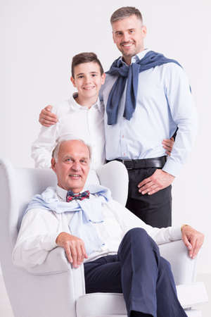 grandkid: Shot of an elderly gentleman sitting in the armchair while his son and grandson standing behind him Stock Photo