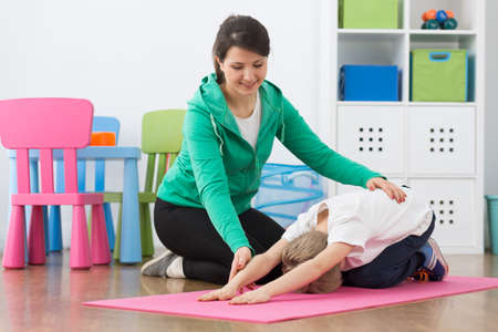 posture correction: Shot of a little boy stretching on a mat and his physiotherapist sitting next to him