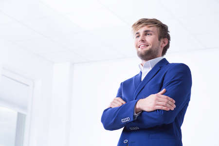 businessman suit: Handsome businessman in a blue suit posing in a light office