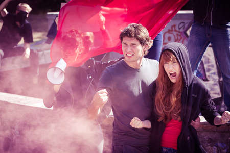 Rebellious couple shouting and raising fists in the middle of a demonstration Stock Photo
