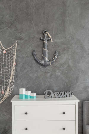 amenities: Anchor decor hanging on the wall above the white commode