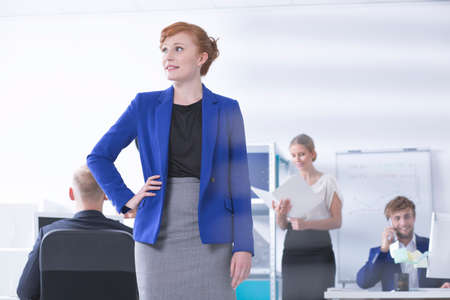 Shot of an elegant businesswoman, in the background office workers during work