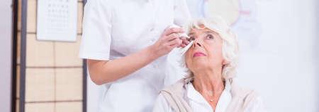eye doctor: Shot of an eye doctor applying eye drops to her patient
