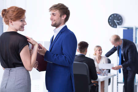 flirt: Young man and woman flirting with each other at work Stock Photo