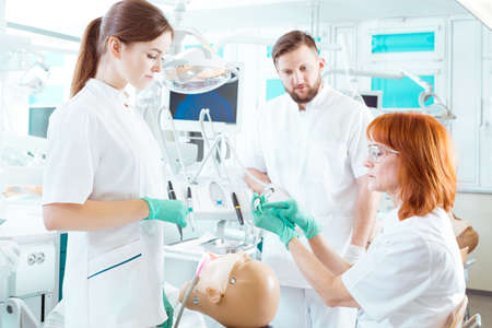 Stomatology teacher presenting the use of a dental drill to her students Stock Photo