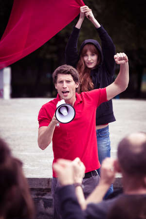 Young leader of a demonstration shouting something through a megaphone