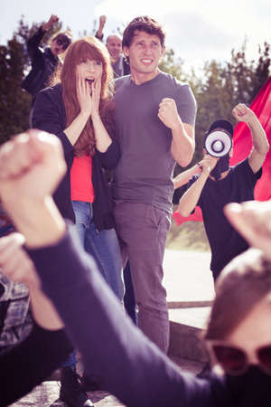 anarchist: Young couple with scared faces, participating in a protest rally