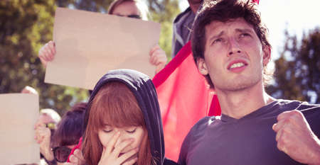 Young couple with pessimistic faces on a protest march