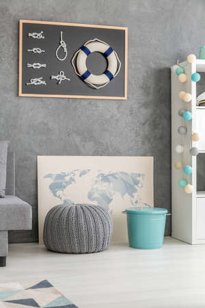 blue bin: Pouf, blue bin and map in frame located on living room floor Stock Photo