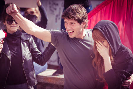 protester: Young protester with his girlfriend, shouting slogans during a demonstration