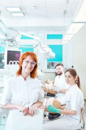 Stomatology academic teacher in a fully-equipped classroom with her students