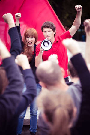 slogans: Young activists shouting slogans through a megaphone during a rally