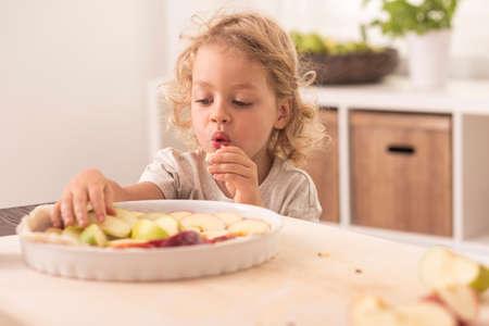 grandkid: Cute small boy tasting a fruit cake