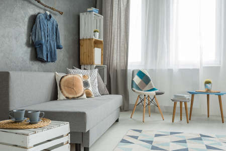 window shades: Modern minimalistic living room interior in shades of cyan with sofa with cushions, chair, coffee tables, stillage made of wooden cases and window with curtain