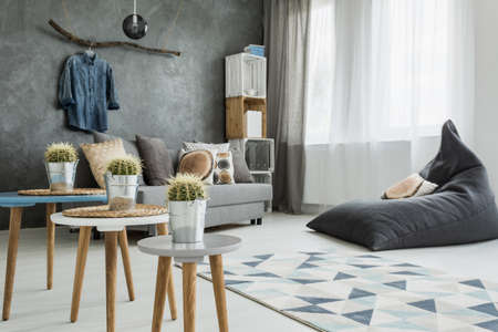 table decoration: Modern minimalistic and bright living room in shades of cyan with sofa, bean bag chair, three coffee tables with cactuses on, carpet and stillage made of wooden cases Stock Photo