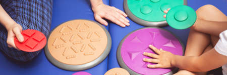 Child during sensory integration therapy touching a colorful tactile disc, panorama