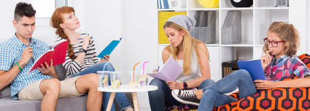 students group: Group of students learning together for a test, sitting in light home interior, panorama