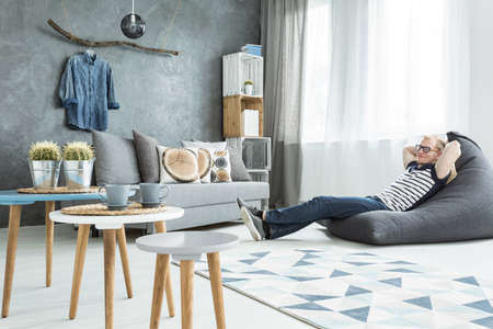 Modern minimalistic and bright living room in shades of cyan with sofa, three coffee tables, carpet, stillage made of wooden cases and a man sitting on a bean bag chair