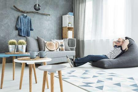 Modern minimalistisch en lichte woonkamer in de kleuren cyaan met een bank, drie salontafels, tapijt, stellage gemaakt van houten kisten en een man zittend op een zitzak Stockfoto