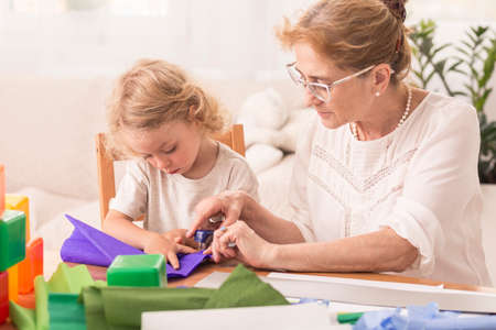 Creative mature woman and small child doing handicrafts together