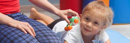 Pequeña niña y su terapeuta tocando el fondo con un dispositivo de masaje, panorama Foto de archivo - 62408847