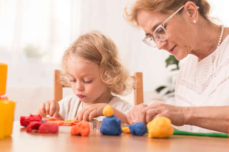 grandkids: Mature babysitter and small boy making figures from a plasticine Stock Photo