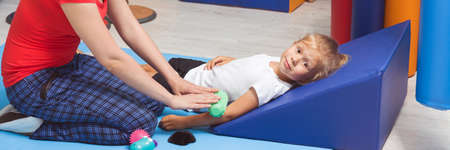 Therapist and small girl lying on a floor during therapeutic sensory massage, panorama
