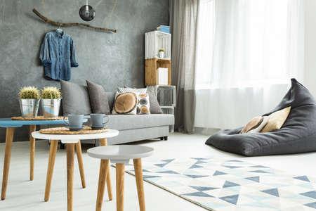 Moderno minimalista e luminoso soggiorno in tonalità di ciano con divano, di fagiolo sedia del sacchetto, tre tavolini, tappeti e borlande fatte di casse di legno