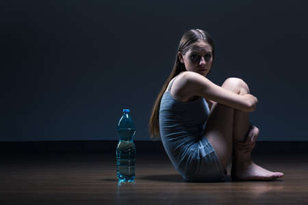 Dark room interior with young girl sitting back to the bottle of water