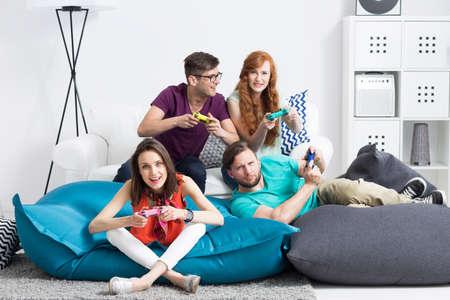 jugando: Grupo de jóvenes amigos que se sientan en pufs modernas, jugando juegos de video