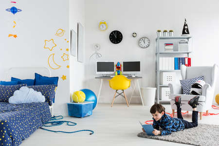 moon chair: Shot of a fully furnished room for a young astronaut with cosmic themes on the wall and with a boy reading a book Stock Photo