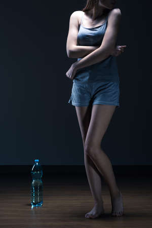 Skinny teenager standing on the floor  with the bottle of water