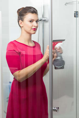 pedant: Woman standing in bathroom and cleaning the shower Stock Photo
