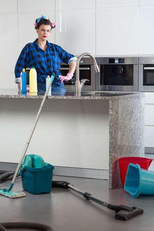 pedant: Woman with curlers standing in the messy kitchen