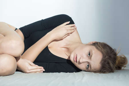 obsession: Young upset woman in black body lying curled up on the floor Stock Photo