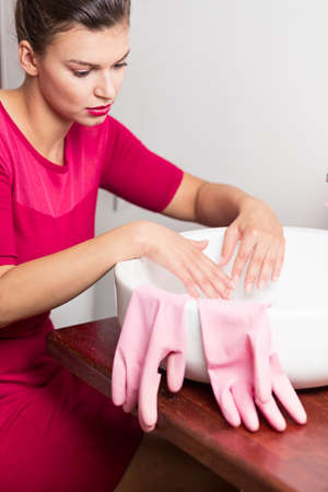 pedant: Woman in pink dress cleaning her hands in a basin Stock Photo