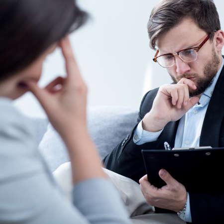 psychiatrist: Psychiatrist talking with despair businesswoman in his office
