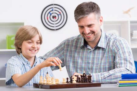 jugando ajedrez: Disparo de un poco de ajedrez niño jugando con su padre Foto de archivo