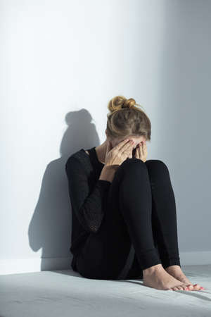 Young, black dressed woman sitting on the floor and covering her face
