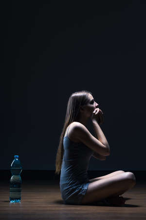 drained: Dark interior with young woman abstaining herself from shouting