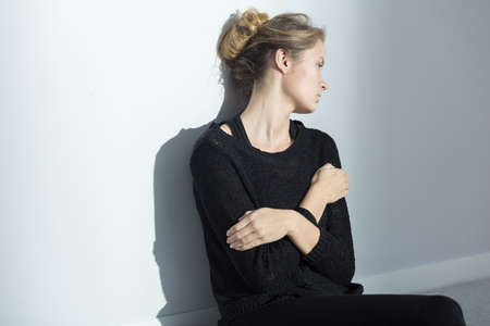 striving: Upset woman with folded arms, looking sadly backwards