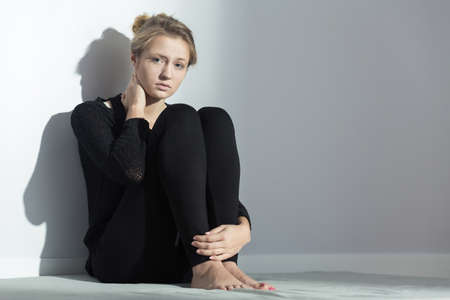 Black dressed girl sitting on the floor in bright interior