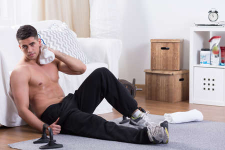exhaustive: Young and fit guy having rest after an exhausting training