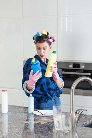 pedant: Woman comparing the etiquettes of two cleaning products Stock Photo