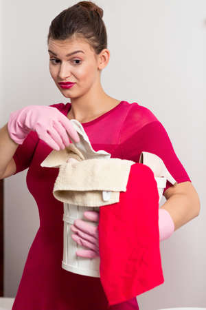 pedant: Disgusted woman with rubber gloves looking at the socks Stock Photo