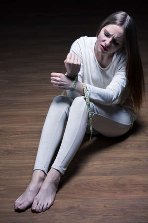 striving: Young woman sitting on the floor with the hands tied by a centimeter