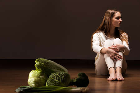 Green vegetables lying on the floor with the young woman sitting behind Banco de Imagens