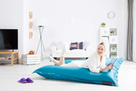 bean bag: Women wearing robe with towel on head lying on a bean bag and reading a book, light home interior