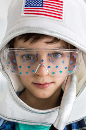 Portrait of a boy with an astronaut helmet with USA flad and glasses with blue stars Stock Photo