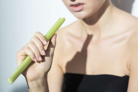 drained: Closer shot of womans hand keeping the green celery Stock Photo